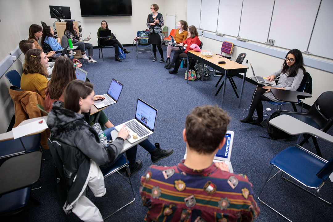 A circle of students sitting at desks in an HSSJ Capstone class