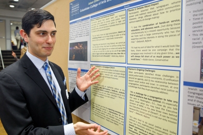 Adam Graubart points to a research poster of his senior thesis